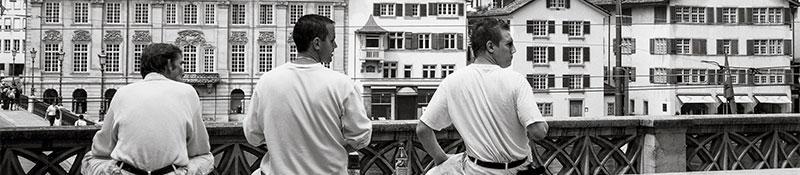 men sitting on a ledge