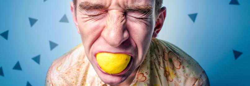 man eating sour lemon